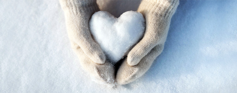 mittens holding snow heart